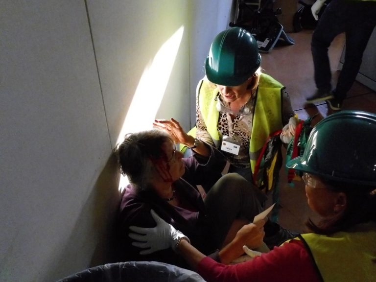 Two CERT trainees assess a victim during the final drill.